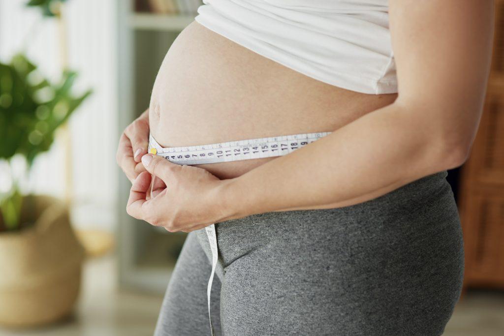 Mujer embarazada pensado si realizarse la abdominoplastia después del parto